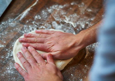 Pizza mit den Händen platt drücken