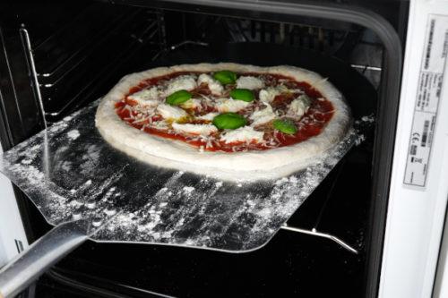 Pizza in den Ofen schieben
